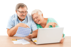 elderly couple looking at coputer