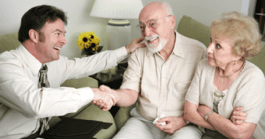 Younger man shaking hands with older couple