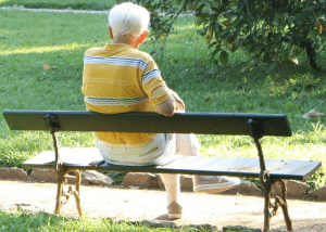 elderly man sitting on a park bench
