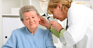 elderly woman getting her ears checked by the doctor